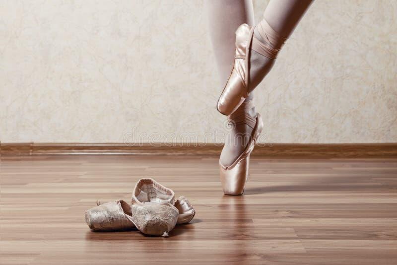 Ballerina i den nya Pointe dansen nära den gamla och sönderrivna Pointen fotografering för bildbyråer