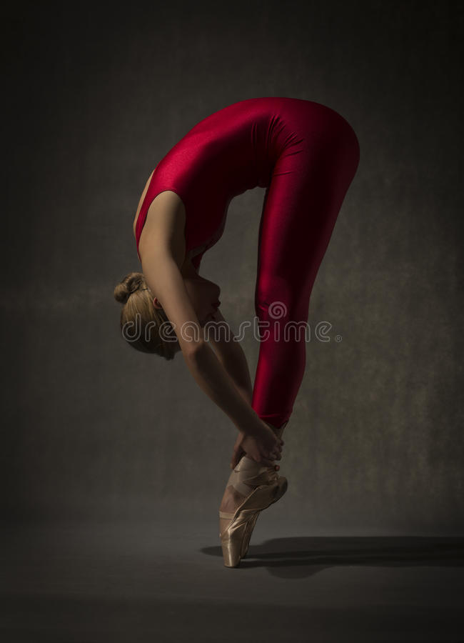 Ballerina i den röda dräkten som poserar på tår arkivfoton