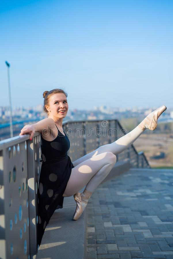 Ballerina i en ballerinakjol som poserar anseende vid staketet Härlig ung kvinna i svart klänning och pointe som dansar yttersida arkivfoto