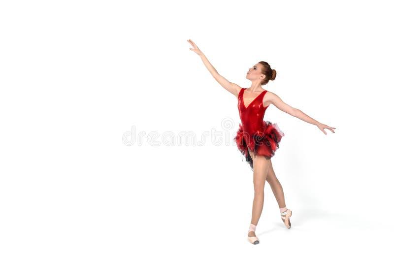 Ballerina i en röd klänning dansar på en vit backgro arkivfoton