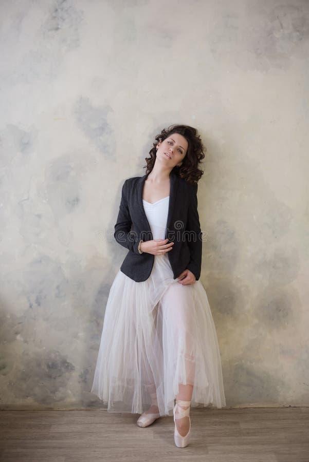 Ballerina i en vit baddräkt och av den långa kjolen med ett härligt kroppanseende på pointeskor arkivbilder