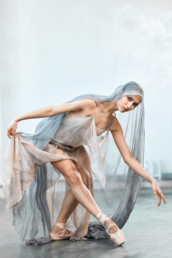Ballerina i l?ng genomskinlig dr?kt f?r etapp som dansar modern balett royaltyfria bilder
