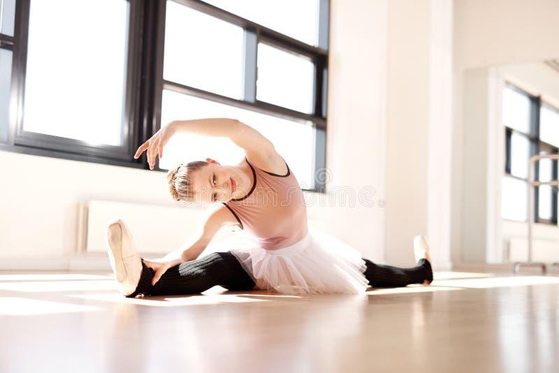 Ballerina i sträckning av genomkörare som ler på kameran arkivbild