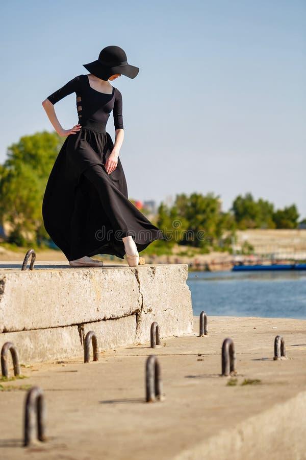 Ballerina im Hut und im langen schwarzen Kleidertanzen auf Pier lizenzfreies stockfoto