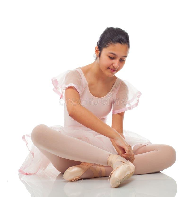 Ballerina, medan binda hans skor för att dansa arkivbild