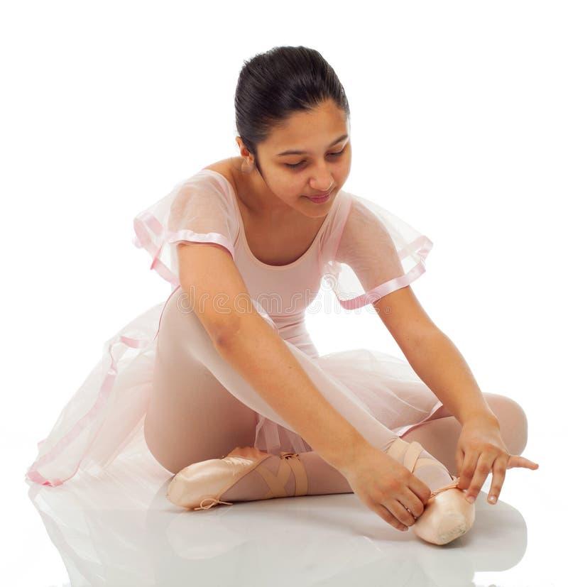 Ballerina, medan binda hans skor för att dansa royaltyfria bilder