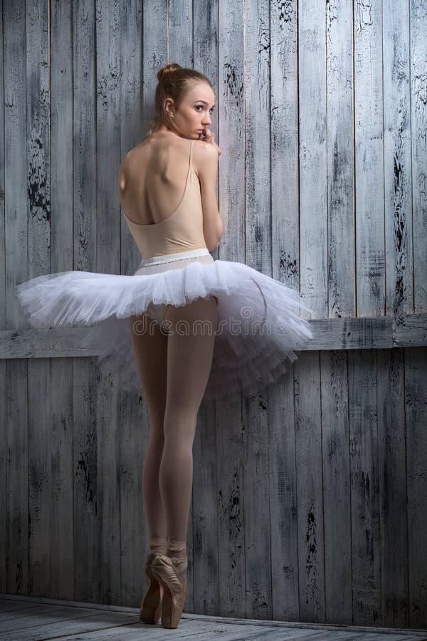 Ballerina modesta che sta vicino ad una parete di legno immagini stock libere da diritti