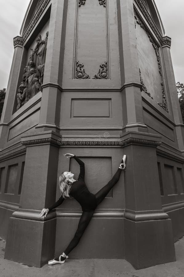 Ballerina på den near svarta väggen för kluven en-pointe royaltyfri foto