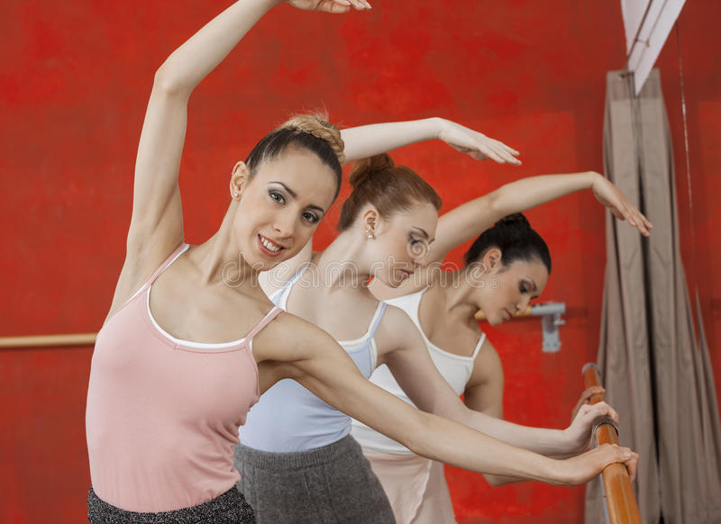 Ballerina Performing With Friends In Dance Studio. Portrait of confident ballerina performing with friends in dance studio stock photo