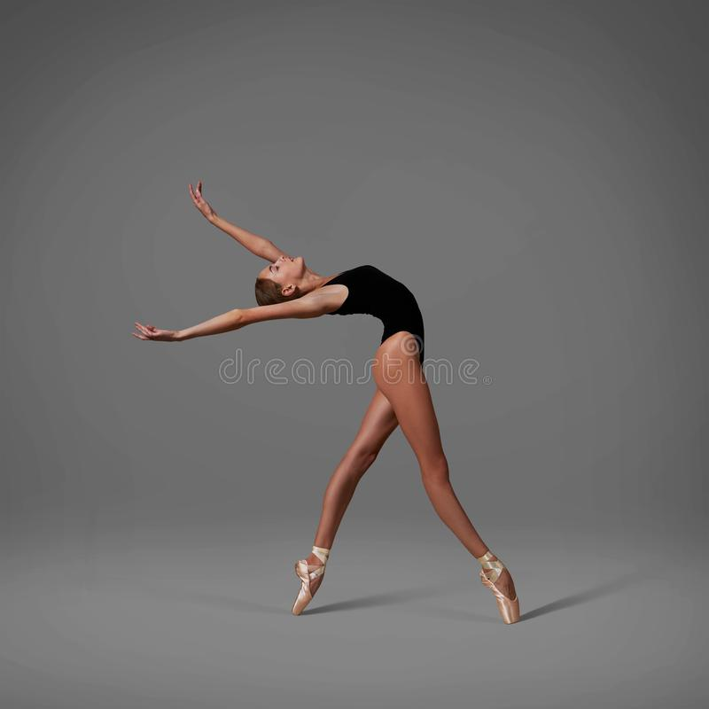 Ballerina makes a back arch. Color photo. Ballerina in pointe shoes and black lingerie makes a back arch. Color photo stock image