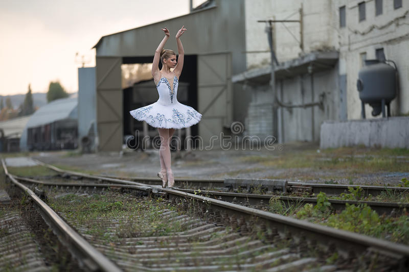Ballerina on rails. Beautiful young ballerina posing on the intersection of railway rails on the background of technical structures. She stands on her toes with stock photo