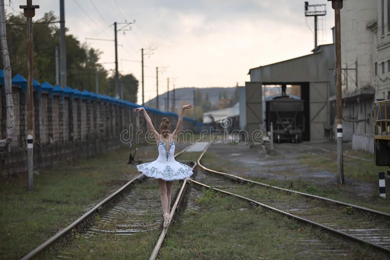 Ballerina on rails. Cute young ballerina posing on the railway rails on the background of technical structures in railway depot. She stands on her toes with her stock photography