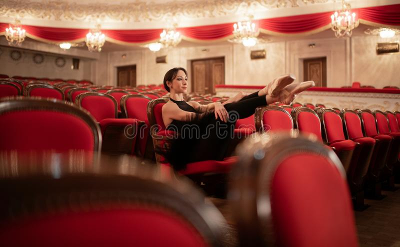 Ballerina Resting In Auditorium after rehearsal. Ballerina Resting In Auditorium in the theatre after rehearsal royalty free stock images