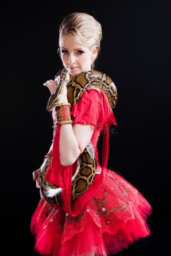 Ballerina in rode kleding met python stock foto