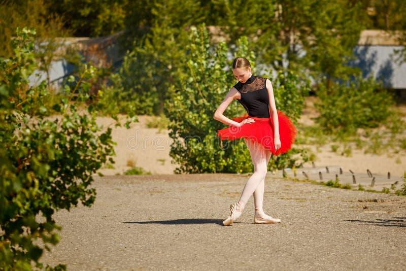 Ballerina in rode tutu die in park danst stock afbeeldingen