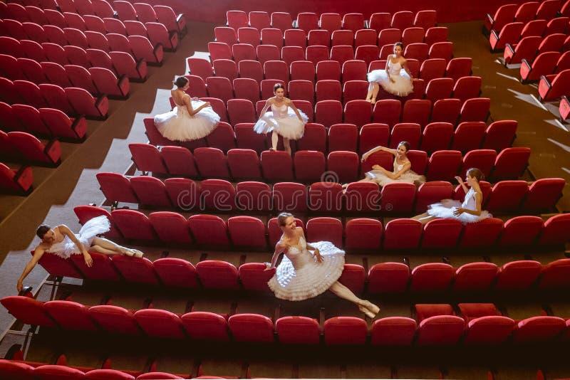 Ballerina's die in het lege auditoriumtheater zitten stock foto