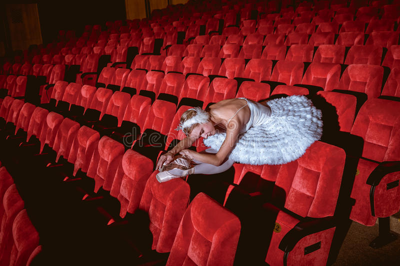 Ballerina sitting in the empty auditorium theater royalty free stock photography