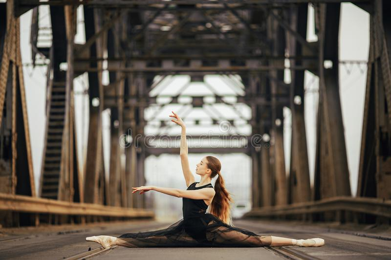 Ballerina sitting in twine pose on the road and rails next to metal supports. Ballerina sitting in twine pose in a black transparent dress on the road and rails royalty free stock image