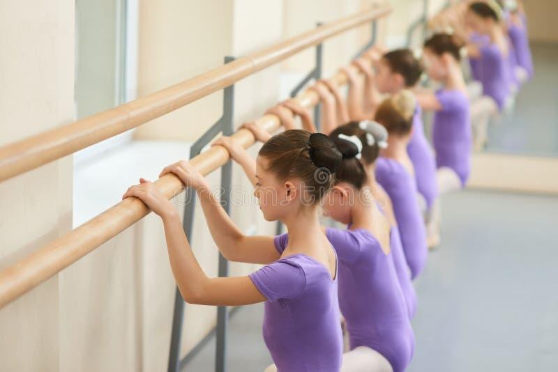 Ballerina som gör övningar på balettbarren royaltyfri foto