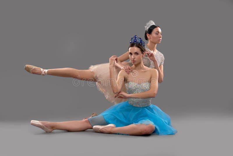 Ballerina som ser kameran medan partner som bakom sitter royaltyfri fotografi