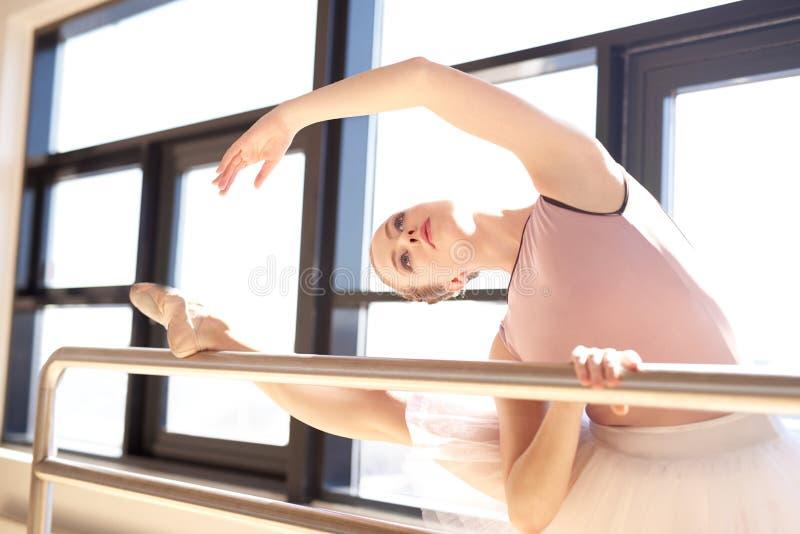 Ballerina som sträcker på barren i dansstudio royaltyfri fotografi