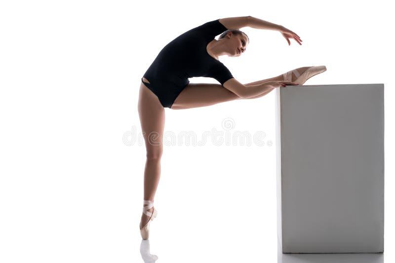 Ballerina som upp sätter hennes ben på kuben, medan värma royaltyfria bilder