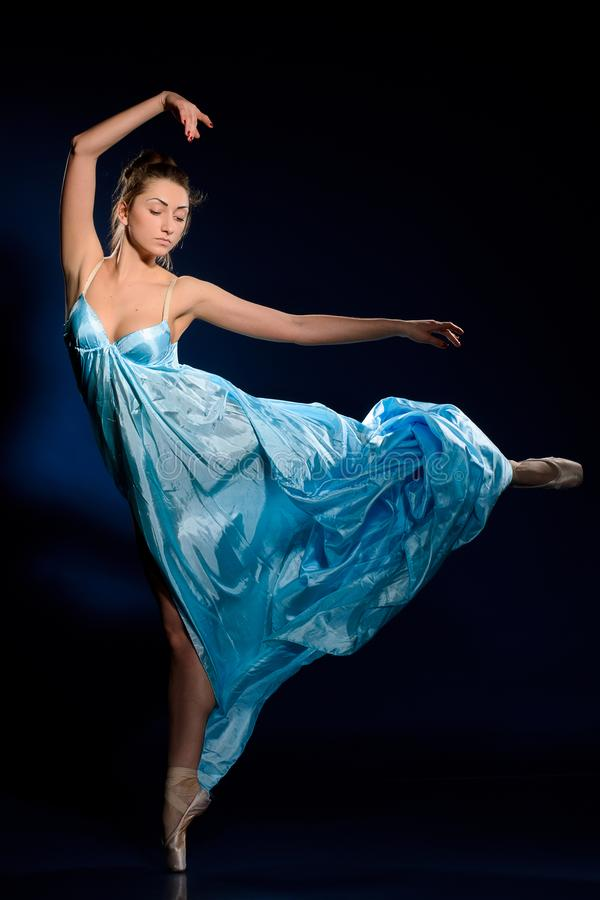 Ballerina springen, die in blauwe kleding vliegen stock afbeelding