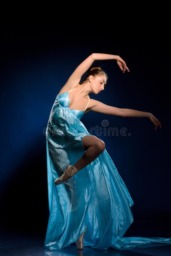 Ballerina springen, die in blauwe kleding vliegen stock afbeeldingen