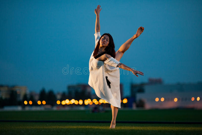 Ballerina steht in der Haltung der Schwalbe auf Rasen am Abend stockfotografie