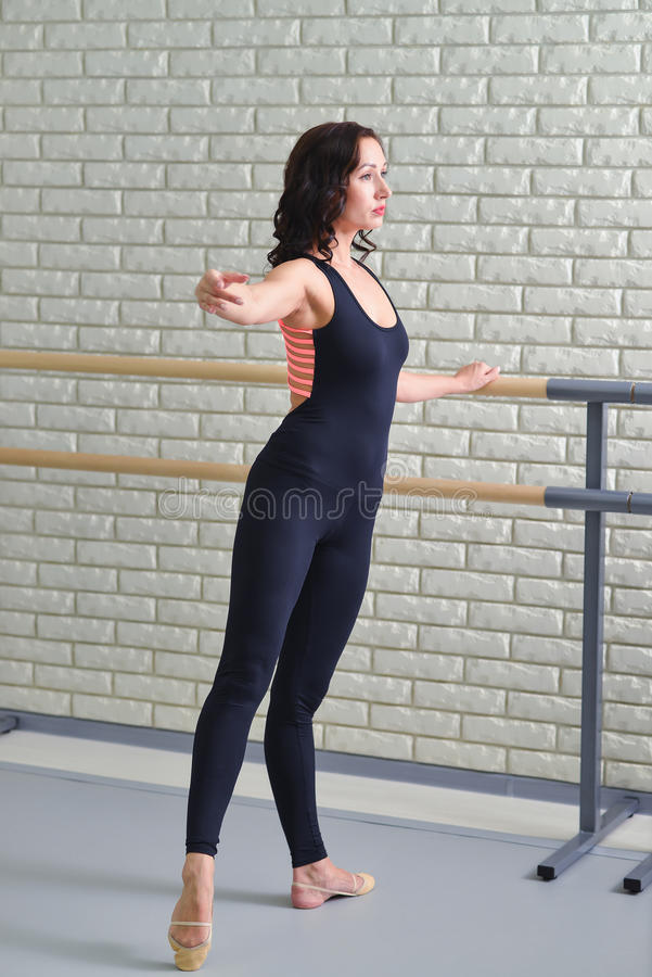 Ballerina stretches herself near barre in the classroom, beautiful women weared in black bodysuit practicing ballet stock images