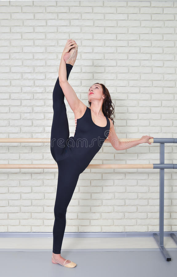 Ballerina stretches herself near barre in the classroom, beautiful women weared in black bodysuit practicing ballet stock image
