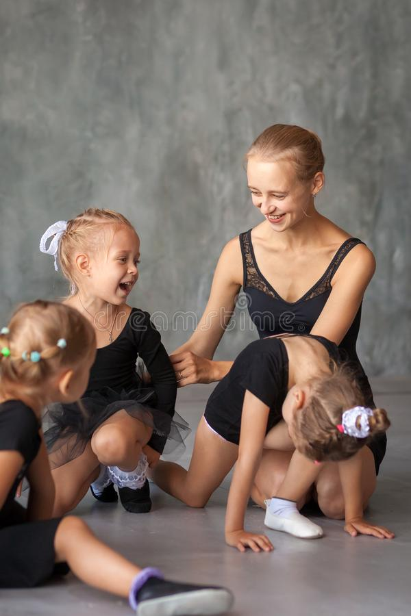 Ballerina teach girls. An adult beautiful ballerina in a black dress, white pantyhose and pointe shoes sits on the floor and talks with little girls about stock photos