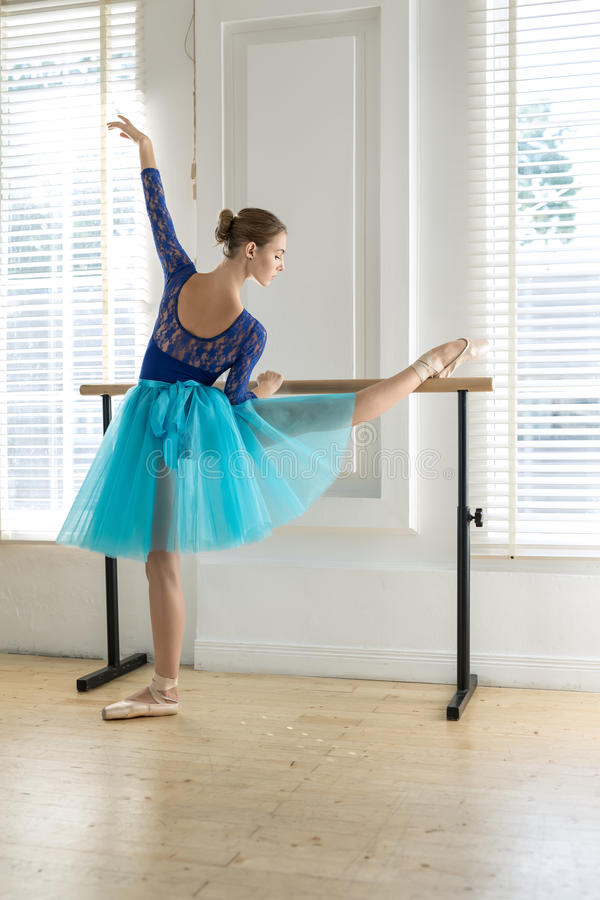 Ballerina is training on barre. Attractive ballerina stands next to the ballet barre and holds right leg and hand on it on the white wall and windows background stock photos