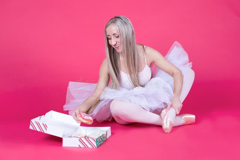 Ballerina in tuturok die voor een doughnut bereiken royalty-vrije stock afbeeldingen