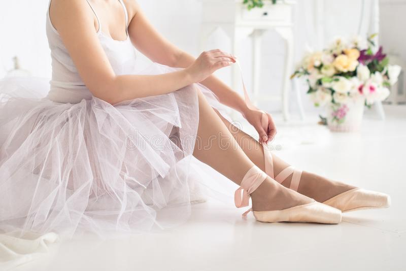 Ballerina tying pointe ballet shoes. Close up stock photo
