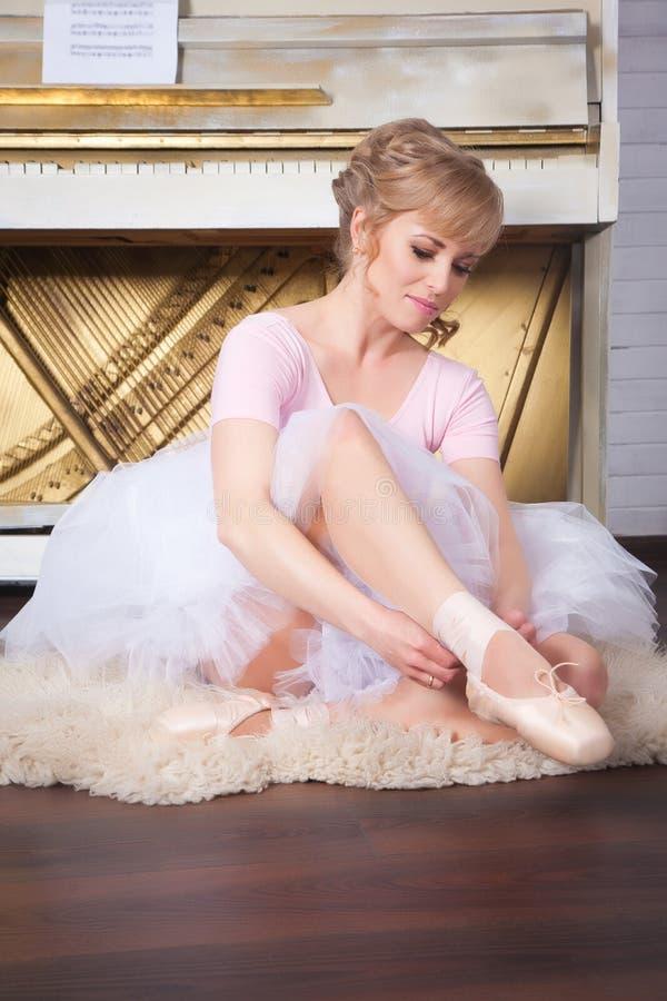 Ballerina tying pointe shoes. In the ballroom stock photos