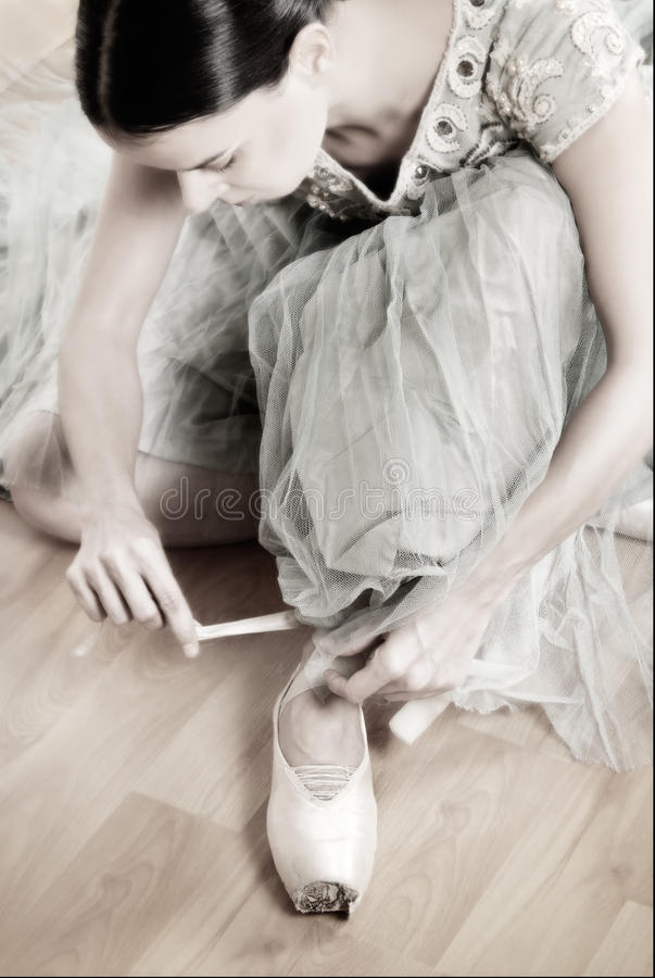 Ballerina tying Pointe Shoes royalty free stock image