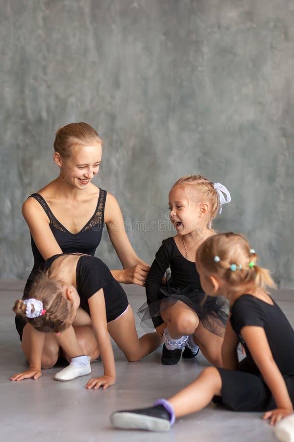 Ballerina undervisar små flickor arkivbilder