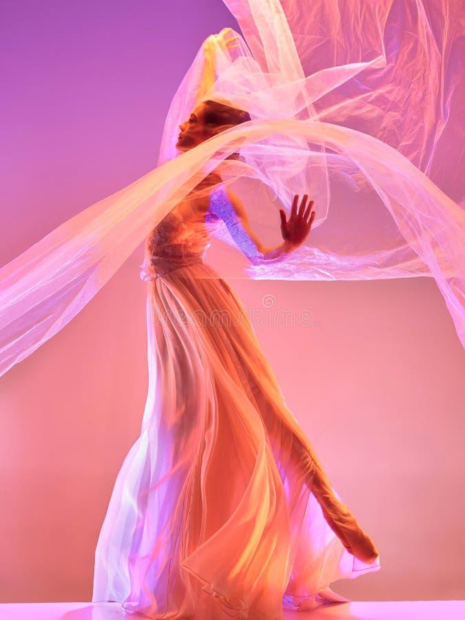 Ballerina Ung behagfull kvinnlig balettdansördans över rosa studio Skönhet av klassisk balett royaltyfria bilder