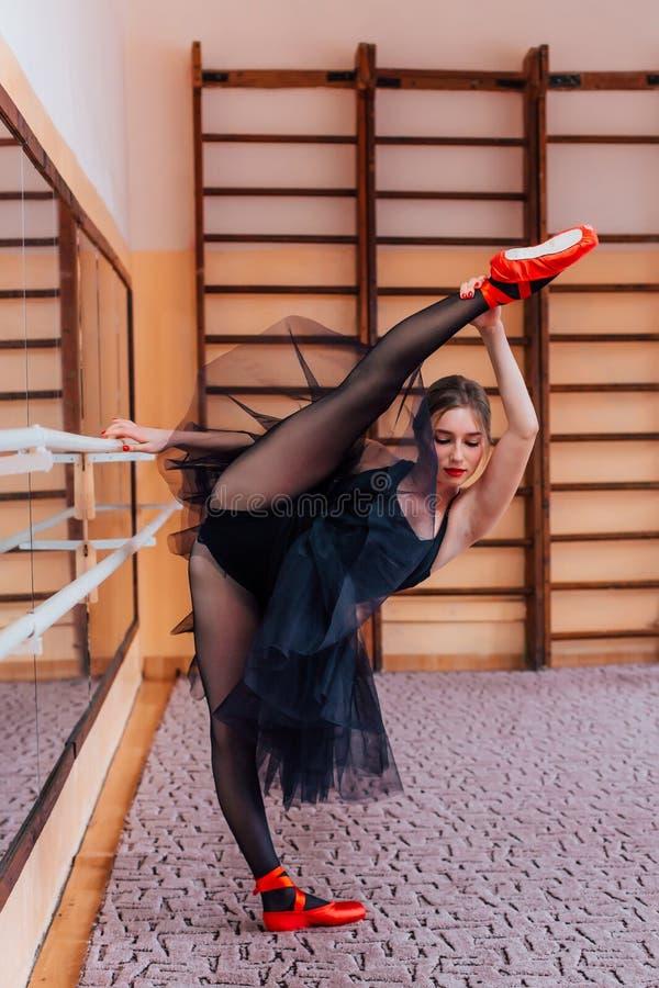 Ballerina Wearing black Tutu make split in training hall. royalty free stock photography