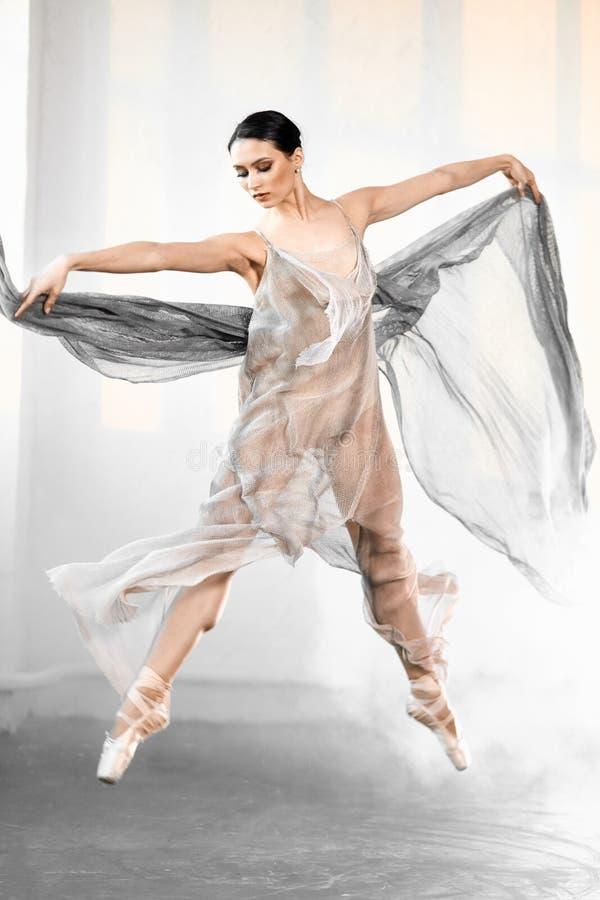 Ballerina, welche die graue transparente Kleidung springt auf Stadium mit Raucheffekt tr?gt lizenzfreie stockfotos