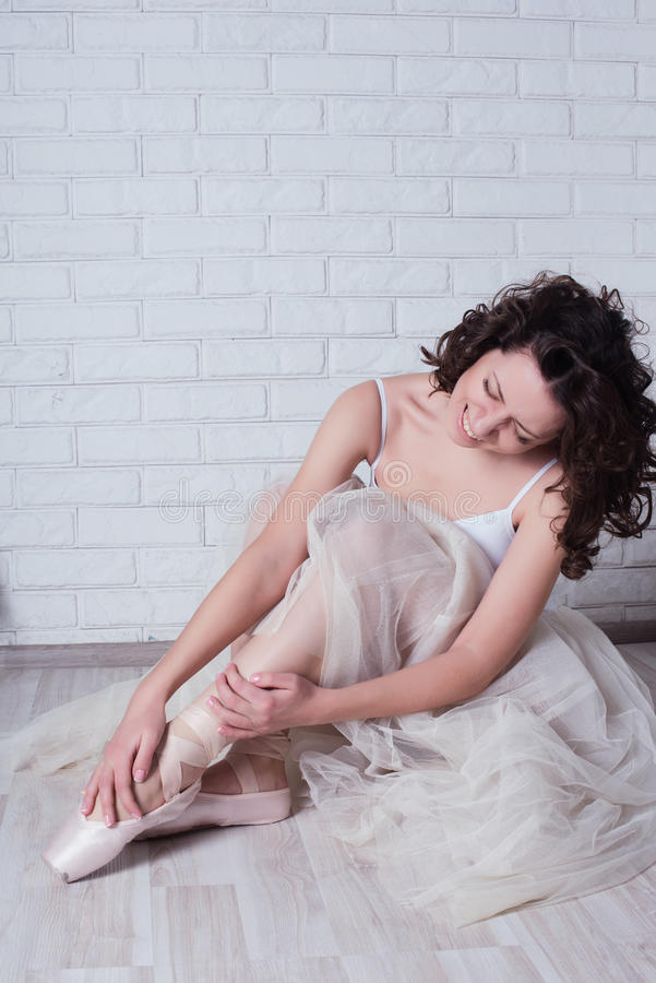 Ballerina in a white bathing suit keeps for aching legs. Pain, injury, lifestyle, hobbies, dancing, choice stock photo