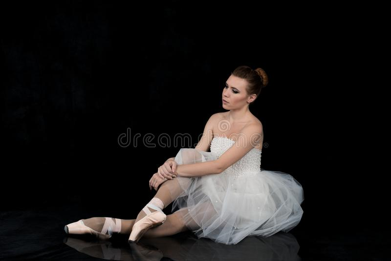 Ballerina in a white classic dress and pointe sits on a reflective surface and rests or plays a role with the performance stock photo