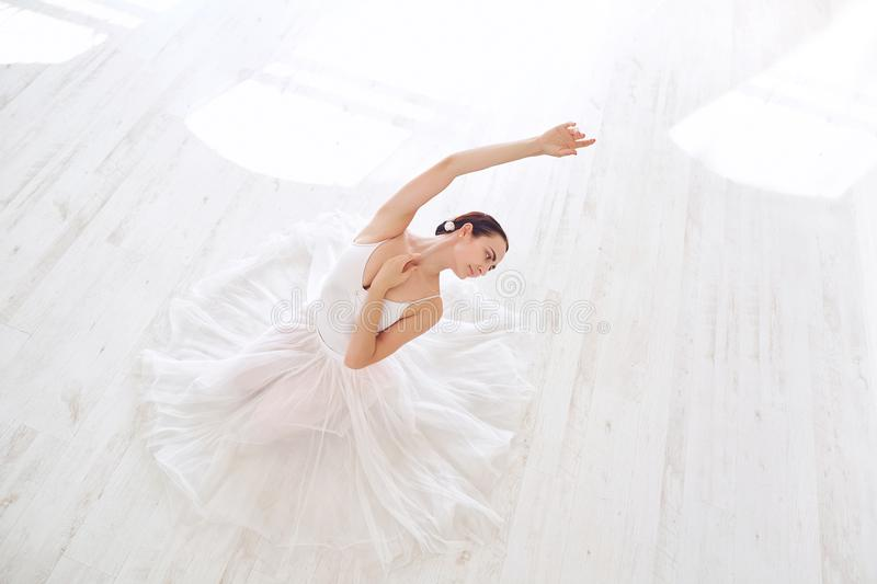 A ballerina in white clothes in a white studio. royalty free stock image