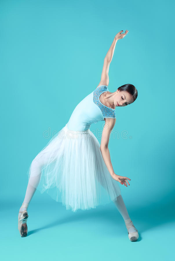 Ballerina in white dress posing on toes, studio background. stock image