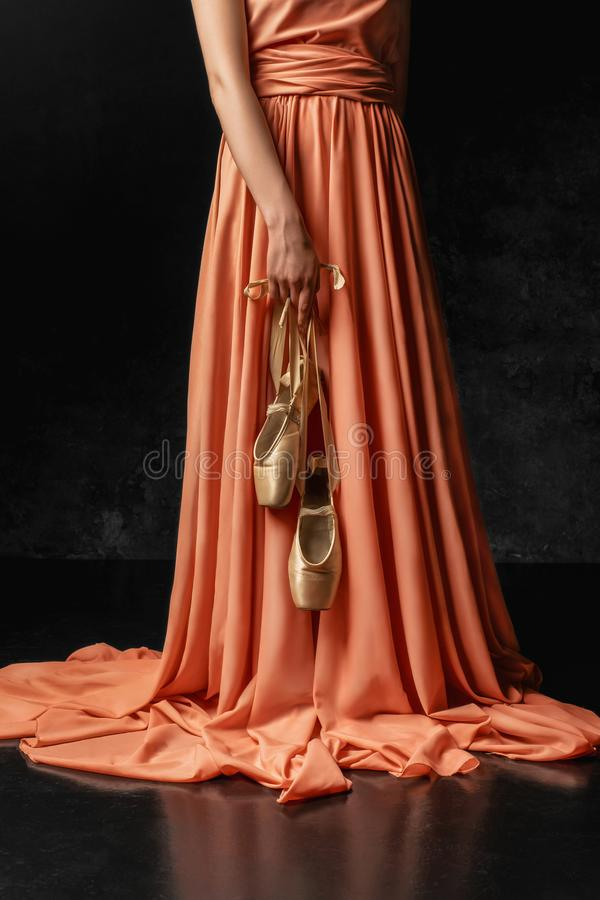 Ballerina. A young  graceful dancer standing against a black wall  dressed in a long peach dress, hands down holding pointe shoes stock photos