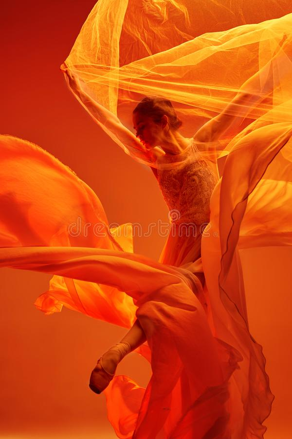 Ballerina. Young graceful female ballet dancer dancing over red studio. Beauty of classic ballet. stock photo