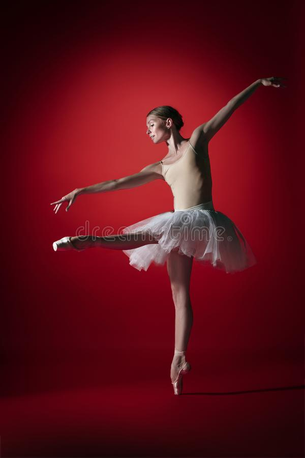 Ballerina. Young graceful female ballet dancer dancing at red studioskill. Beauty of classic ballet. royalty free stock images