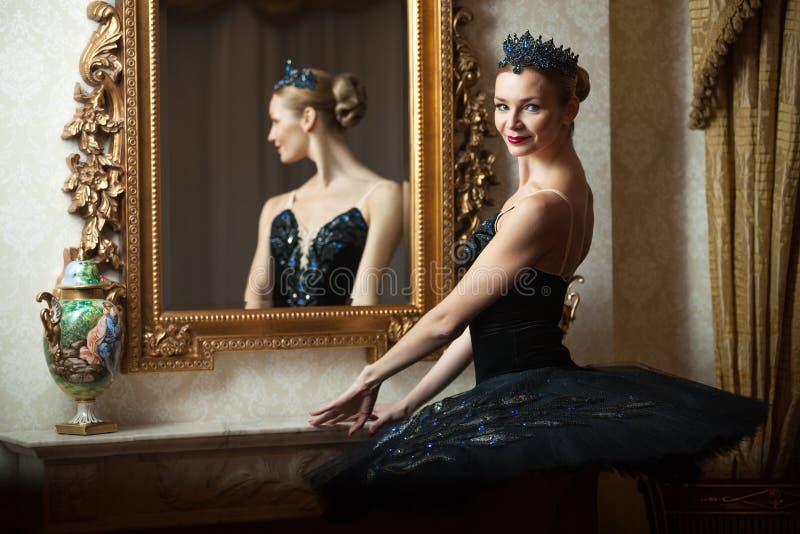 Ballerina in zwarte tutu die zich voor van spiegel bevinden stock afbeelding