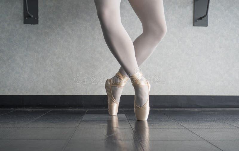 Ballerinadansare i pointen för balettstudioen i den fjärde positionen för releve fotografering för bildbyråer